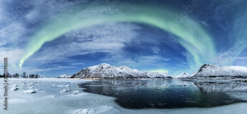 Obraz Wide shot of the arch shaped northern lights over a frozen sea with the snow covered mountains - fototapety do salonu