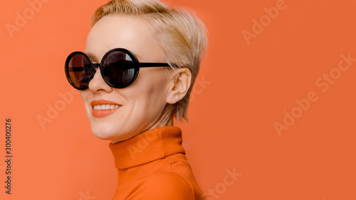 Fotomural Beauty portrait of female model wearing trendy sunglasses over orange background