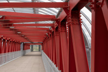 Pedestrian Crossing, Construction Of Red Metal Structures. The Roof Is Made Of Steel Channels Connected To Each Other. Red Iron Beams On Boltsю