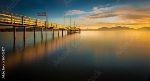 Blurred reflection of the beautiful sunrise in the sky and the pier in the calm blue sea