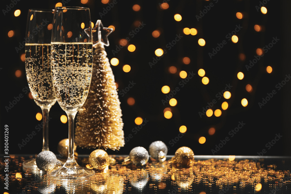 Fototapety, obrazy: Champagne glasses and baubles against blurred lights background, space for text