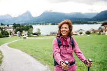 Senior Woman With Nordic Walking Poles Hiking In Nature, Resting.