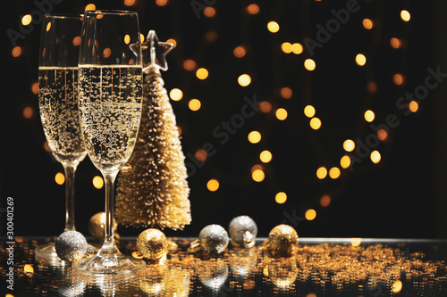 Champagne glasses and baubles against blurred lights background, space for text - 300401269