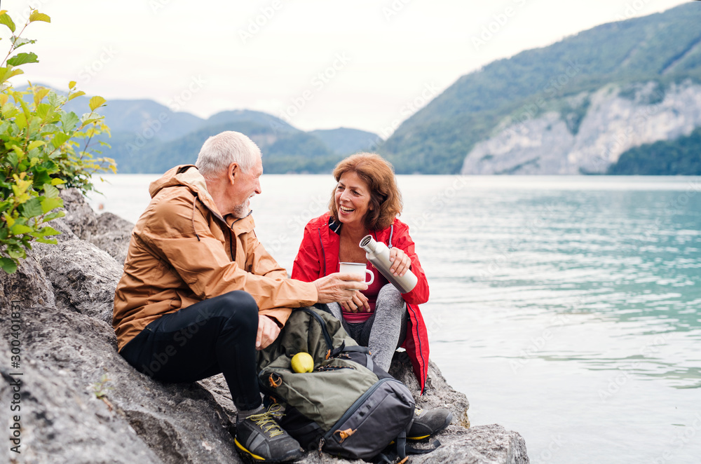 Fototapety, obrazy: A senior pensioner couple hiking by lake in nature, sitting and resting.
