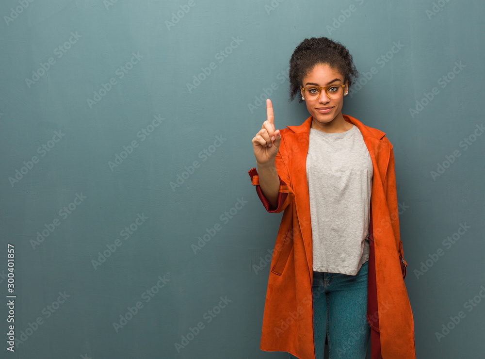 Fototapeta Young black african american girl with blue eyes showing number one
