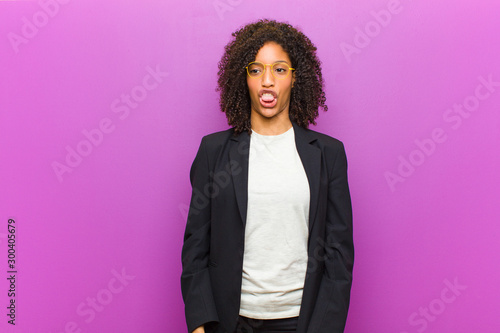 Fotografie, Tablou  young black business woman feeling disgusted and irritated, sticking tongue out,