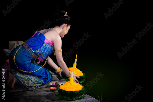 Portrait of beautiful asian woman in Thai dress traditional praying hold kratong Wallpaper Mural