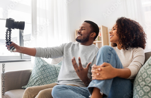 Vászonkép  blogging, videoblog and people concept - happy african american couple of video