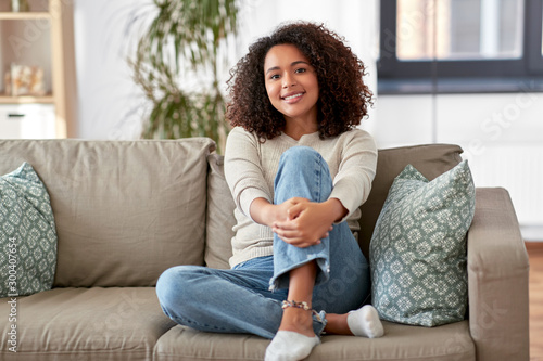 Obraz people, race, ethnicity and portrait concept - happy african american young woman sitting on sofa at home - fototapety do salonu