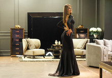 Sexy Blonde Woman In A Black Evening Dress Posing In A Furniture Store