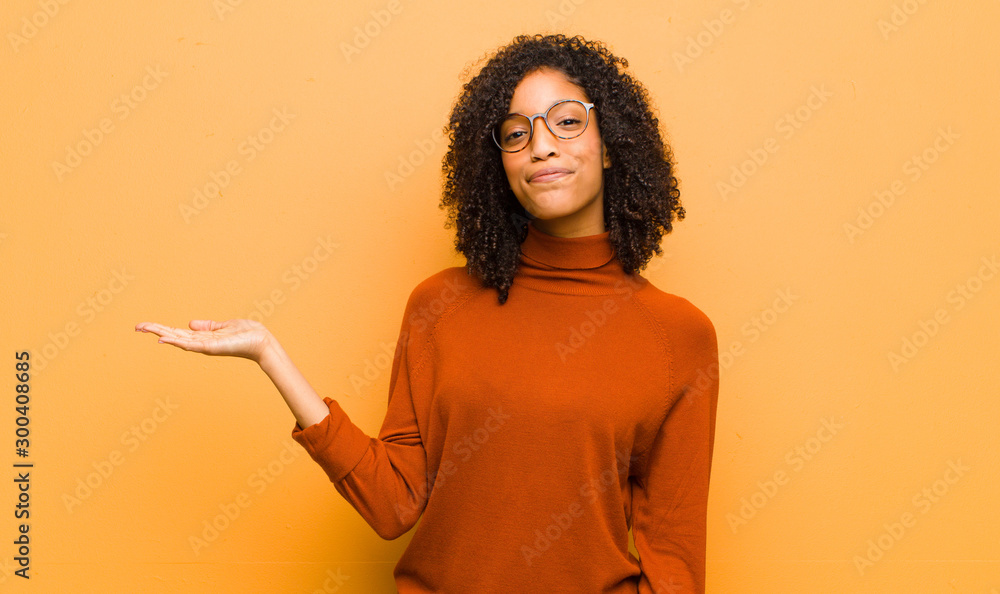 Fototapeta young pretty black woman feeling happy and smiling casually, looking to an object or concept held on the hand on the side against orange wall