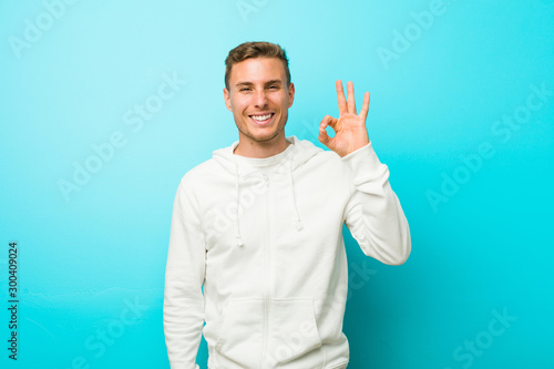 Fotomural  Young caucasian sport man cheerful and confident showing ok gesture