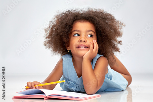 Obraz childhood, creativity, drawing and people concept - happy little african american girl with sketchbook and pencil over grey background - fototapety do salonu