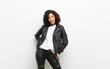 Leinwandbild Motiv young pretty black woman wearing a leather jacket against white wall