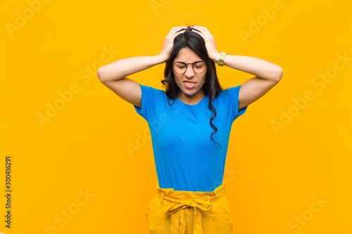 Carta da parati  young pretty latin woman feeling stressed and frustrated, raising hands to head,