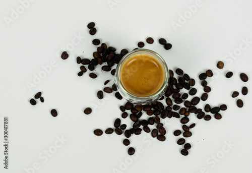 Espresso in modern cup on white background with coffee beans