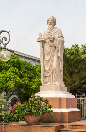 Da Nang, Vietnam - March 10, 2019: Closeup of cream-colored statue of Saint Paul with his sword and epistle backed by green foliage and under silver sky Canvas Print