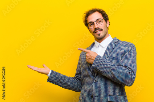 Obraz young handsome man smiling, feeling happy, carefree and satisfied, pointing to concept or idea on copy space on the side against orange wall - fototapety do salonu