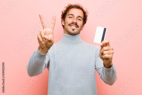 Fototapeta  young handsome man with a credit card against pink flat wall