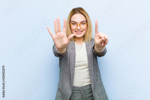 Fotografía  young pretty blonde woman smiling and looking friendly, showing number six or si