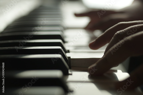 children's hands are playing the piano - 300424868