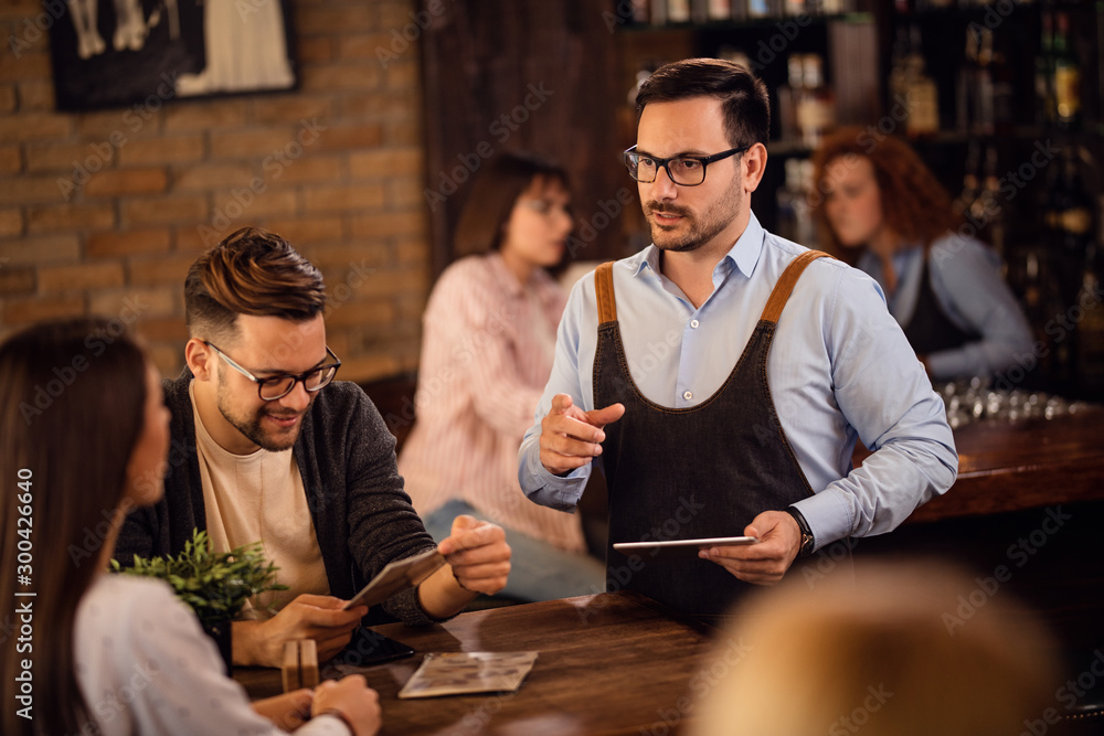Fototapeta Mid adult waiter communicating with customers in a pub.