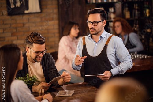 Mid adult waiter communicating with customers in a pub.
