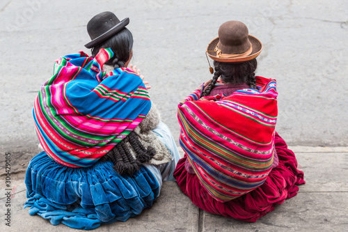 Two women with braids wearing traditional clothes sit on the streets of Puno cit Wallpaper Mural
