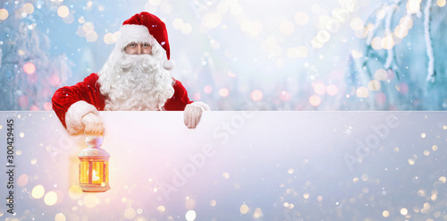 Spoed Fotobehang Kerstmis Santa Claus with a Lamp on a Background of a Snowy Forest