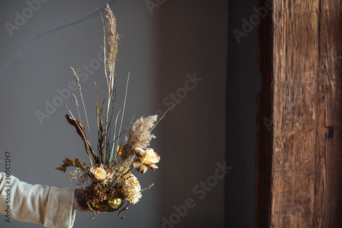 Fototapeta Beautiful autumn bouquet of mixed flowers with dry winds in the hands of a woman. The work of the florist. Beautiful bouquet. Flower delivery obraz