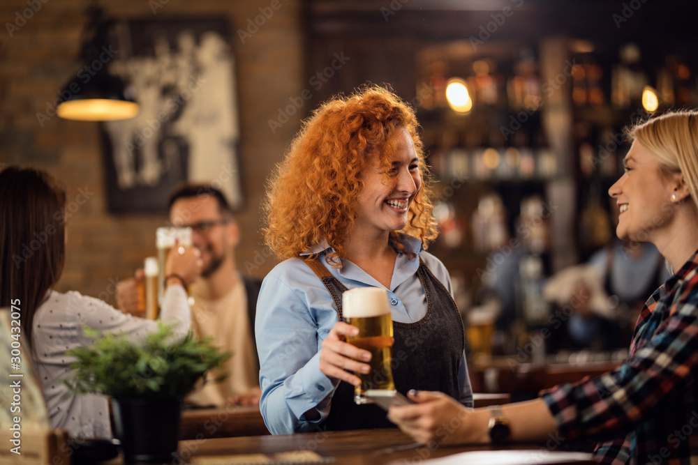 Fototapety, obrazy: Happy waitress talking to a woman while giving her a glass of beer in a pub.