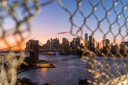 Obraz View of Manhattan and the Brooklyn Bridge through a Manhattan Bridge fence opening in the sunset - fototapety do salonu