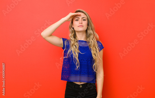 Fototapeta  young blonde woman greeting the camera with a military salute in an act of honor