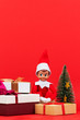 canvas print picture - Christmas background. Stack of Xmas present boxes and sitting toy elf on red background