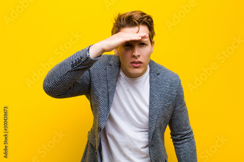 young red head man looking bewildered and astonished, with hand over forehead lo Wallpaper Mural
