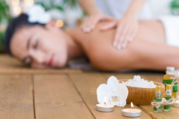 Obraz na płótnie Canvas Closeup burning candles, bottles with aroma oil, bowl with salt. Young pleased woman is getting thai massage, therapy. Brunette girl is lying on couch in spa ayurveda salon. Relax and health care.