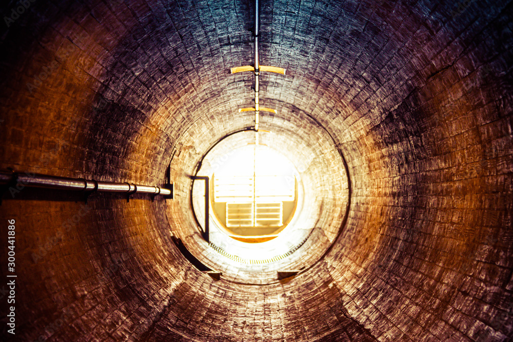 Fototapeta Staring down an old tunnel with a light at the end of the tunnel.  This is a ventilation tunnel inside the Hoover Dam.