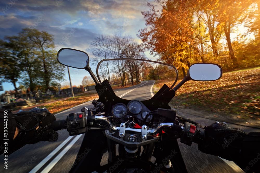 Fototapeta Driving a motorbike on an autumn sunny day