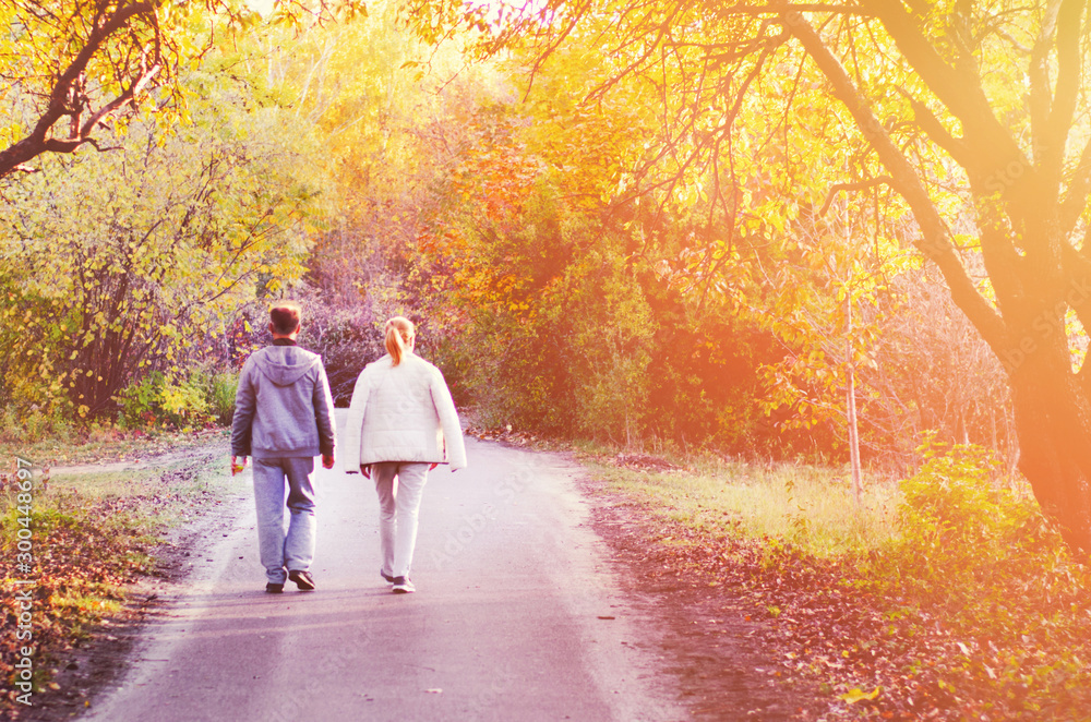 Fototapety, obrazy: Two people, man and woman walking in autumn park with yellow, red and orange trees, falling leaves and bright sun beams. Seasonal concept. Fading and lifestyle concept. Back side view.