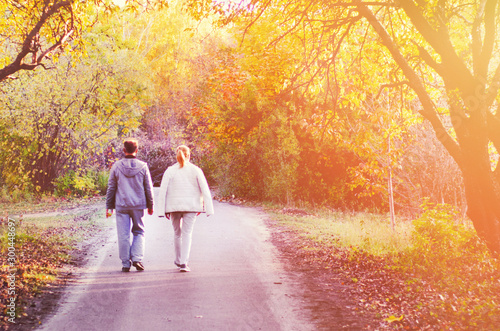Photographie  Two people, man and woman walking in autumn park with yellow, red and orange trees, falling leaves and bright sun beams