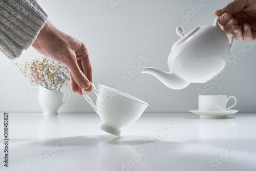 Fotografía Composition with white porcelain tea-ware on a light gray background with a deli