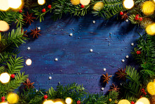 Christmas Background, Frame Made Of Fresh Yew Branches, Anise Stars And Twinkling Lights On Navy Blue Wooden Background, Copy Space.