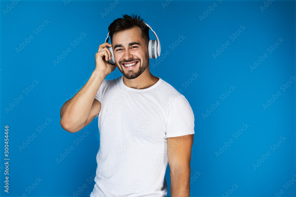 Fototapeta Cute european man smiles and listens something in the headphones