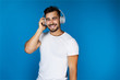 canvas print picture - Cute european man smiles and listens something in the headphones