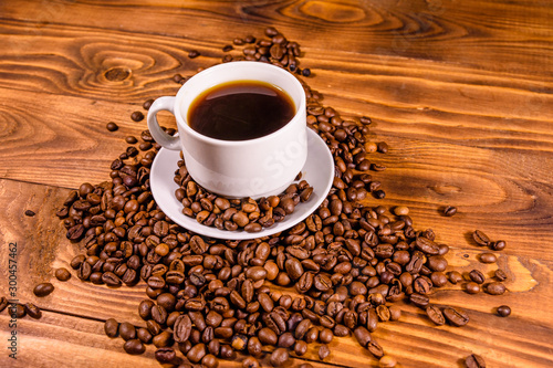 Canvas Prints Cafe Cup of hot coffee and scattered coffee beans on wooden table