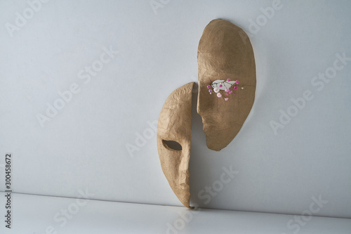 Fotografia Composition with half of the paper masks on a light gray background with a delic