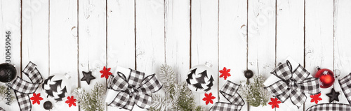 Christmas banner of black and white checked buffalo plaid ribbon, gifts and ornaments. Above view long bottom border on a white wood background.