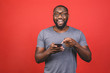 Leinwanddruck Bild - Portrait of handsome excited cheerful joyful delightful african american guy wearing casual sending and getting messages to his lover isolated against red background. Using phone.