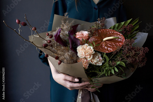 Canvas Print Female hands holding a bouquet decorated in vintage style on a dark background,