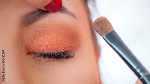 Makeup professional artist applying base color eyeshadow on model eye Tableau sur Toile